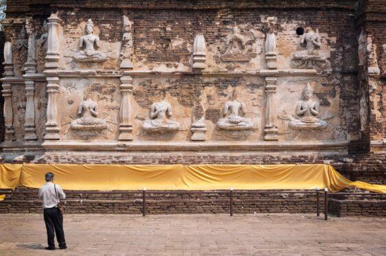 Turista de pie delante del chedi principal en Wat Jet Yod